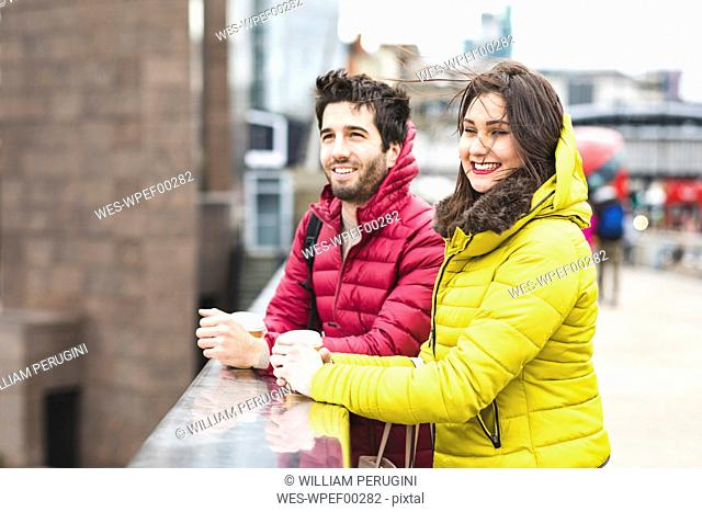 UK, London, young couple with coffee to go standing on bridge