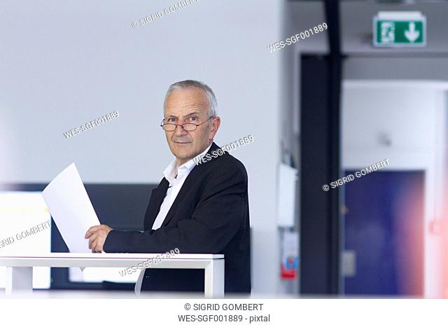 Businessman in open space office holding document