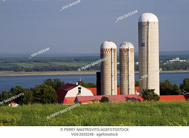 Red and white dairy farm with three grain silos in summer, Saint-Jean, Ile d'Orleans, Quebec, Canada