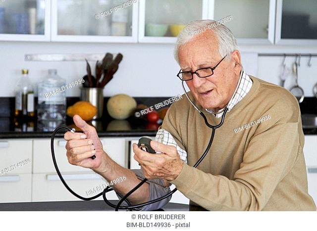 Caucasian man taking his own blood pressure