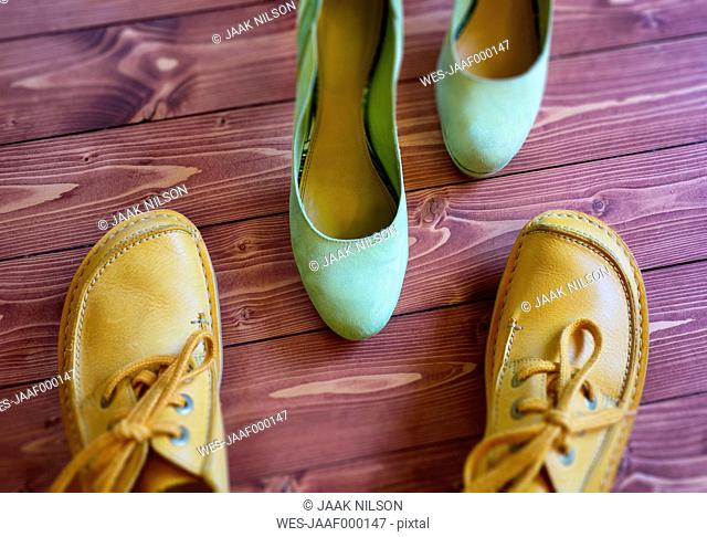 Pair of yellow man's shoe and pair of green lady's shoe on wood