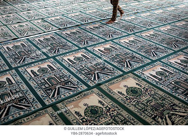 A person walks on top of Muslim praying carpets inside the Grand Mosque in Medan, Sumatra, Indonesia