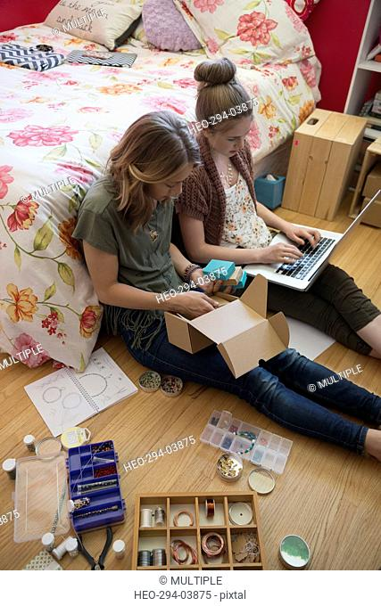 Girls using laptop and making jewelry on bedroom floor