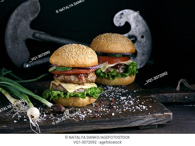 double burger with vegetables and cheese on a brown wooden board