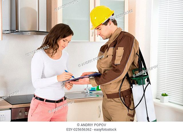 Young Woman Signing Document In Front Of Male Exterminator In Kitchen