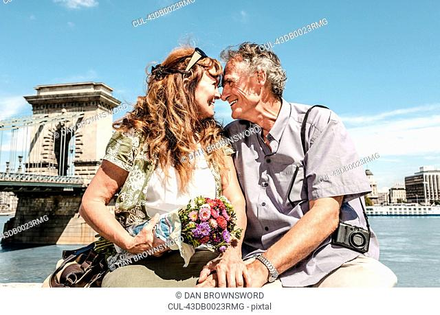 Older couple touching noses on bridge