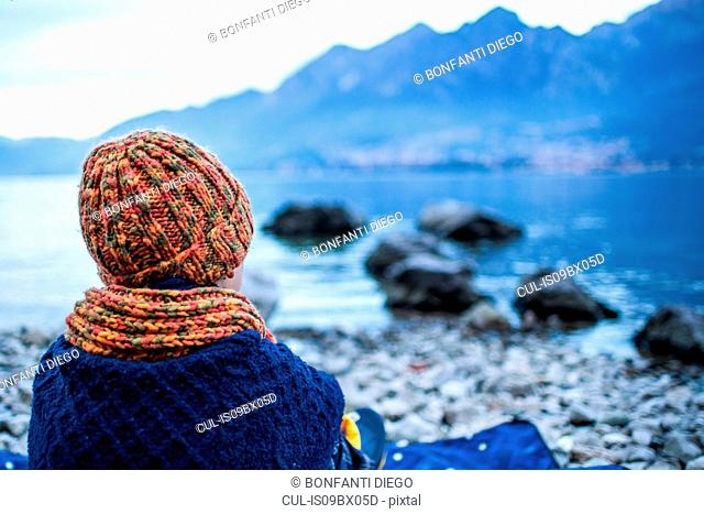 Boy sitting on blanket on lakeside, rear view, Lake Como, Onno, Lombardy, Italy