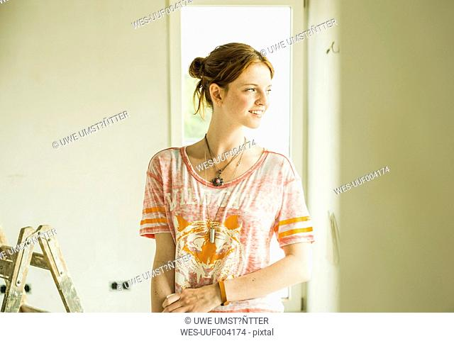Smiling young woman in room with ladder