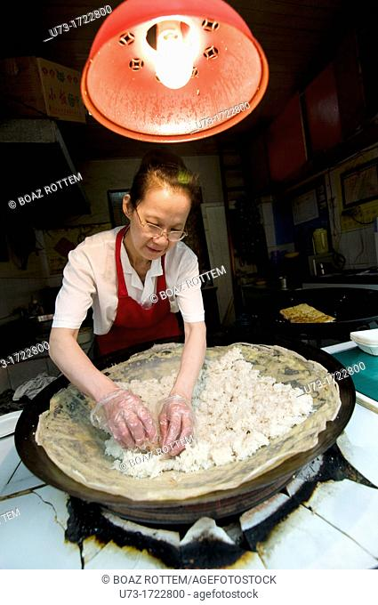 A vendor prepares Dou pi in her street food stall in Wuhan, China