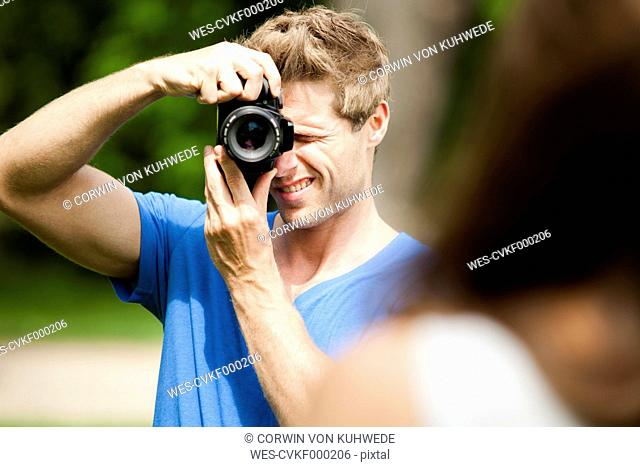Man taking photo of woman outdoors