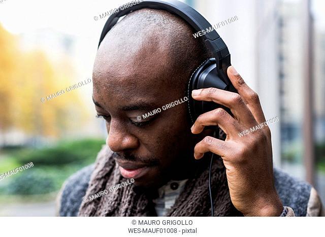 Bald man listening music with headphones