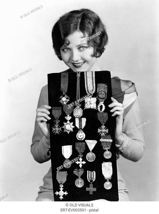 Woman holding display of medals All persons depicted are not longer living and no estate exists Supplier warranties that there will be no model release issues