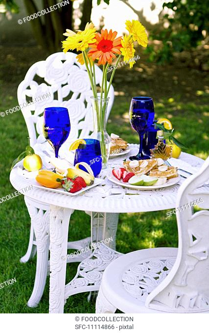 Outdoor Table Set with a Belgian Waffle Breakfast, Tall Flowers in a Vase on Table