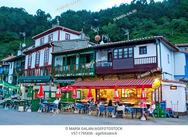 People sitting on a terrace at evening. Tazones, Asturias province, Spain