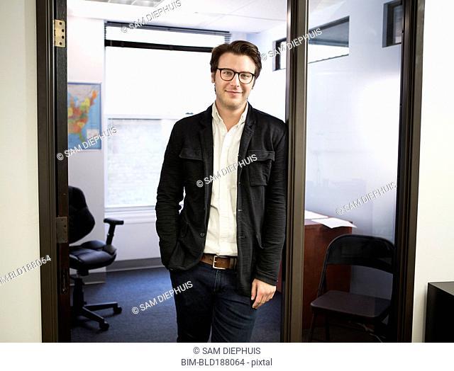 Caucasian businessman smiling in office doorway