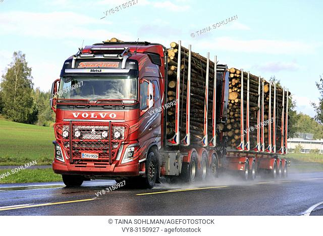 SALO, FINLAND - SEPTEMBER 22, 2018: Red Volvo FH16 750 logging truck of Kuljetusliike Seppo Saarinen transports log load on wet road in autumn