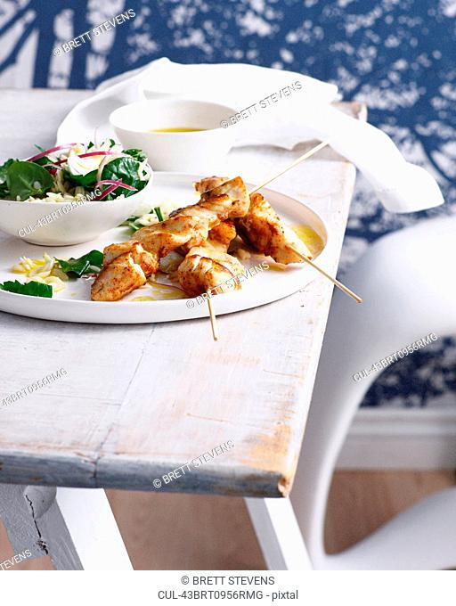 Plate of fish skewers with salad