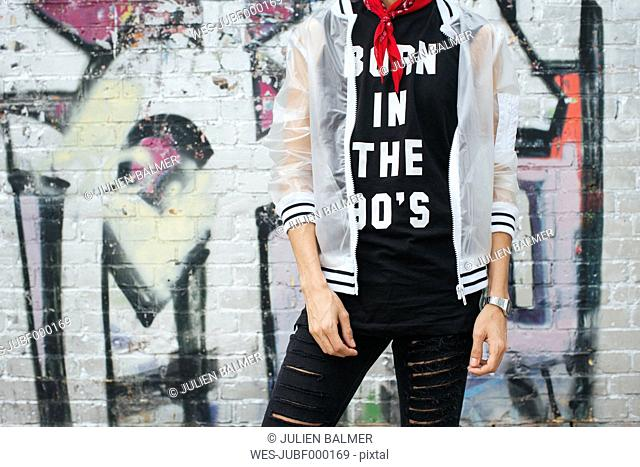 Fashionable young man wearing t-shirt with saying 'Born in the 90s' and rainjacket, partial view