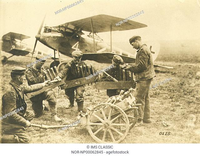 Soldiers loading ammunition for a biplane