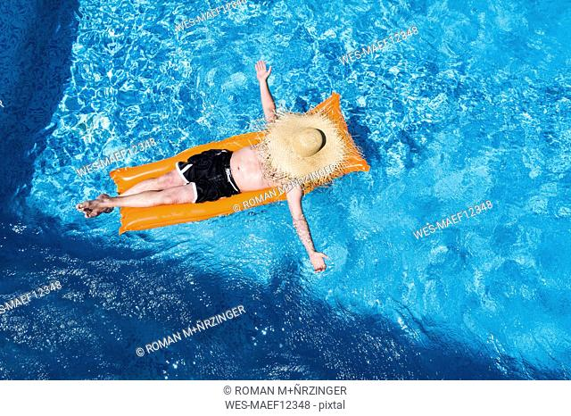 Man relaxing on orange airbed in swimming pool