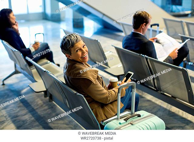Commuter with coffee cup using mobile phone in waiting area