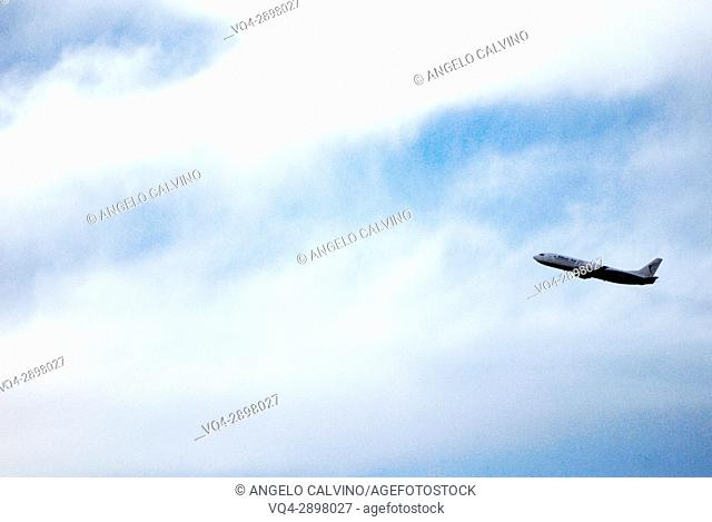 Airplane flying in clouded blue sky