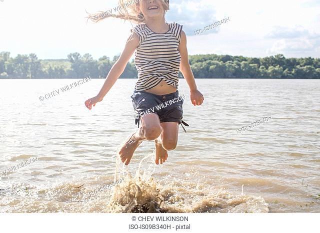 Girl jumping and splashing in river