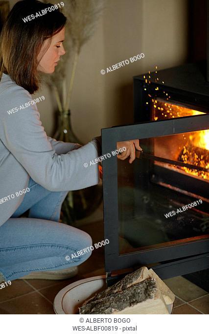 Woman using fire hook for poking open fire