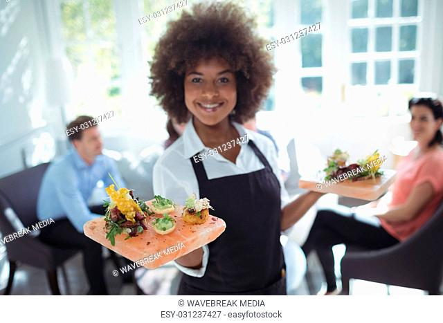 Portrait of smiling waitress holding food tray