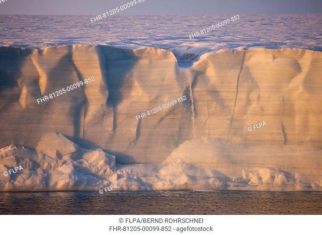 Coastal glacier terminus with waterfall from melting ice at sunset, Brasvellbreen Glacier, Nordaustlandet, Svalbard, august