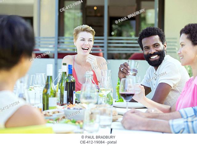 Friends talking at table outdoors