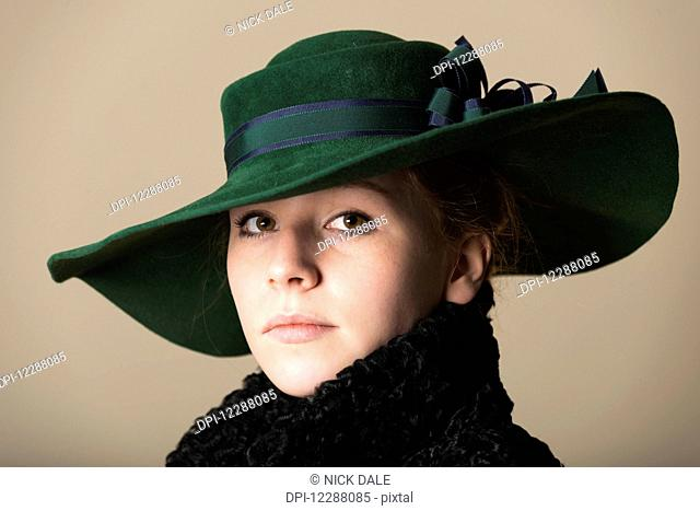 Portrait of a young woman with red hair looking serious in a black overcoat with the collar turned up and a green wide-brimmed hat with a blue and green ribbon;...