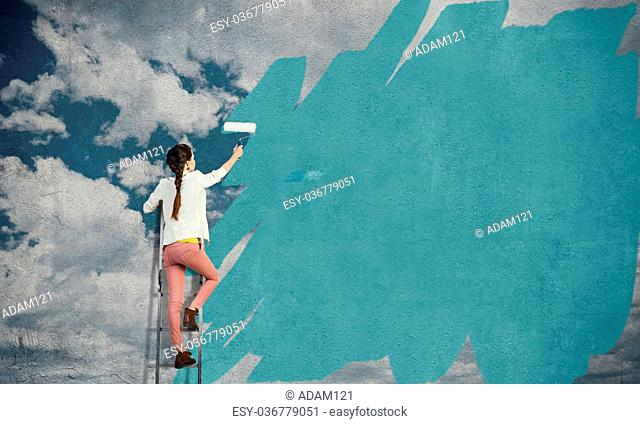 Young woman standing on ladder and painting wall