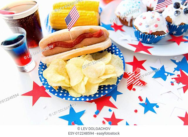 national holidays, celebration, food and patriotism concept - close up of hot dog with american flag decoration, potato chips and drinks on 4th july at party on...