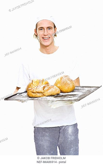 Studio portrait of male baker holding tray with bread