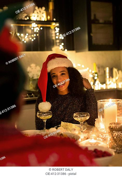 Smiling woman wearing Santa hat at candlelight Christmas dinner party
