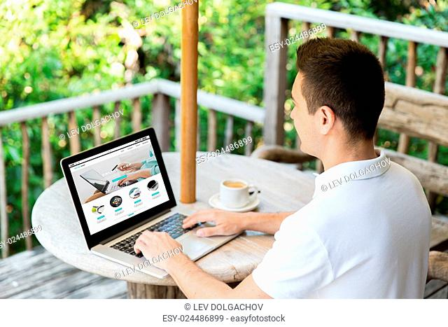 business, internet shopping, people and technology concept - close up of businessman with online shop web page on laptop computer screen on summer terrace...
