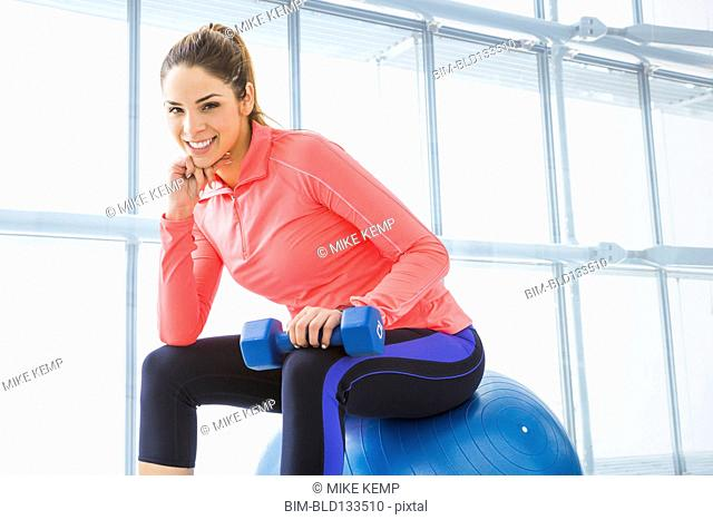 Mixed race woman sitting on exercise ball in gym