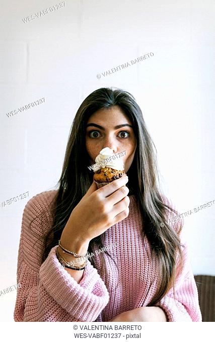 Young woman eating a cup cake with whipped cream