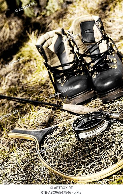 Close-up of a fishing rod with a fishing net and a pair of shoes