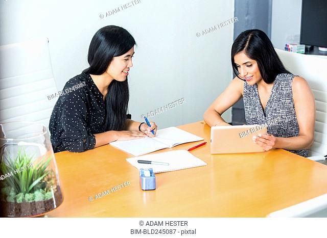 Women using digital tablet in meeting