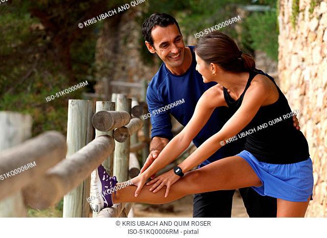 Couple stretching on rocky coastline