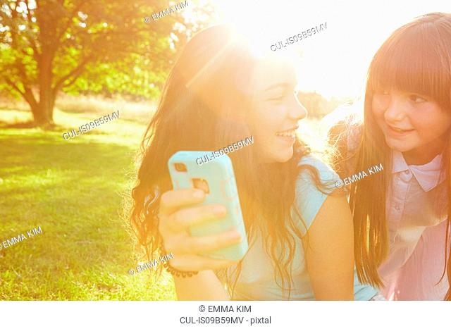 Two girls looking at smartphone in sunlit park