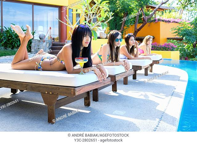 Multiple attractive young women lying on loungers, tanning and watching others next to a swimming pool of an upscale residence in Mexico