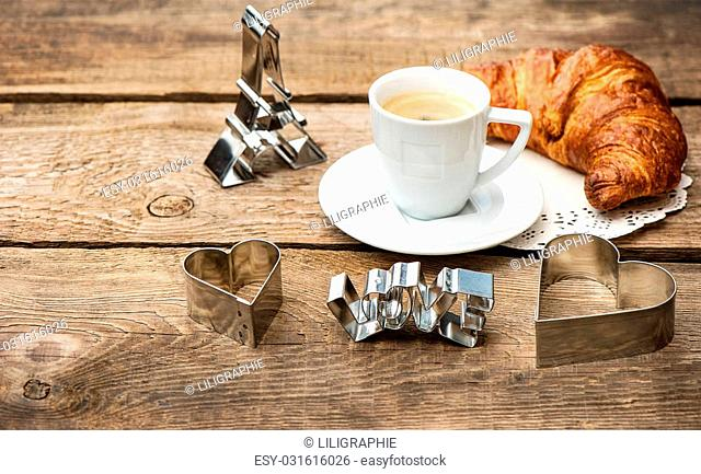 Cup of black coffee with croissant and heart decoration on rustic wooden background. romantic french breakfast with deco symbol of paris eiffel tower