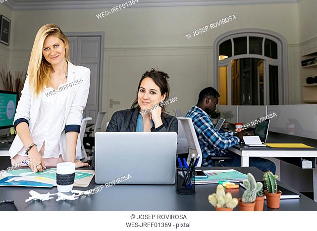 Young businesswomen working together, using laptop, colleague sitting in background
