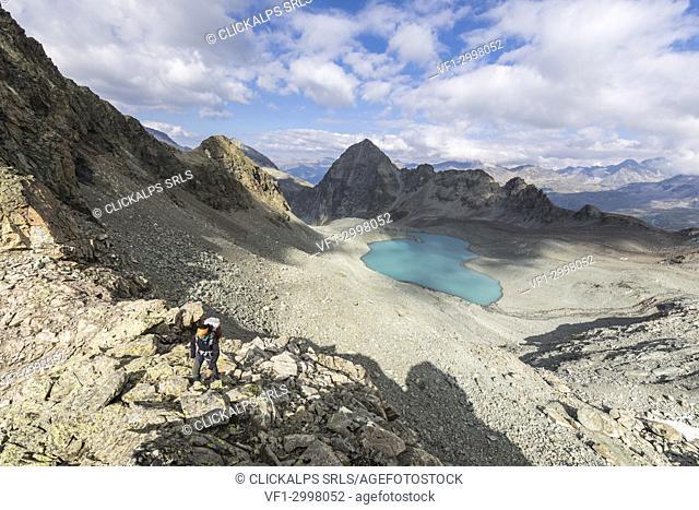 Hiker on rocks around Lej Lagrev, Silvaplana, canton of Graubünden, Engadine, Switzerland