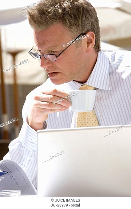 Businessman drinking espresso and using laptop at sunny, outdoor cafŽ