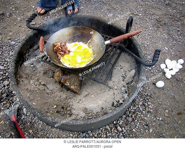 Bacon and eggs over a camp fire