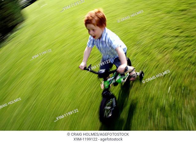 Boy cycling on a bike with stabilisers in Birmingham Park